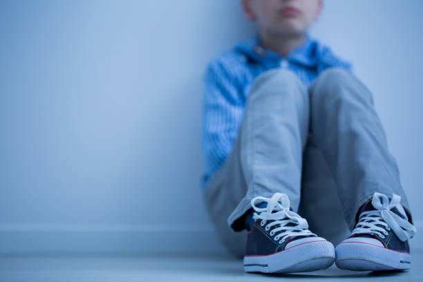 sad boy sits alone - child stock photos and pictures