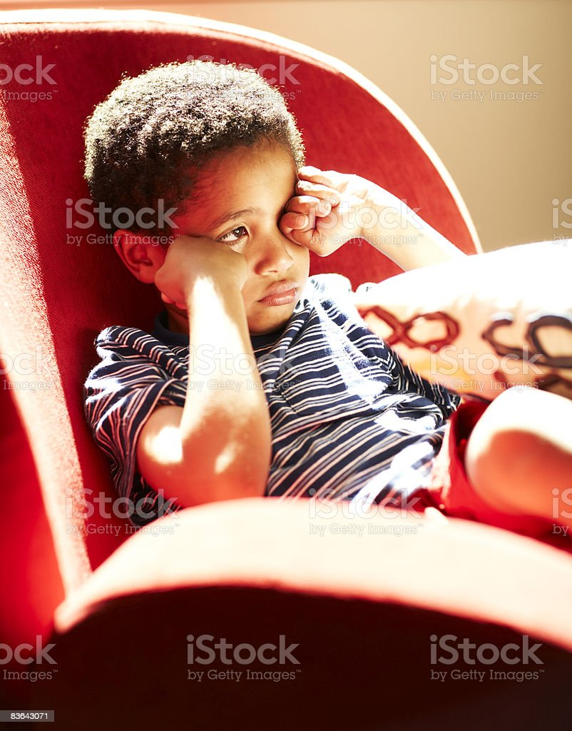 sad boy sitting in chair royalty-free stock photo