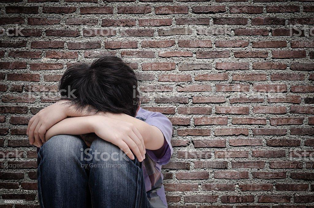 sad boy sitting on floor stock photo