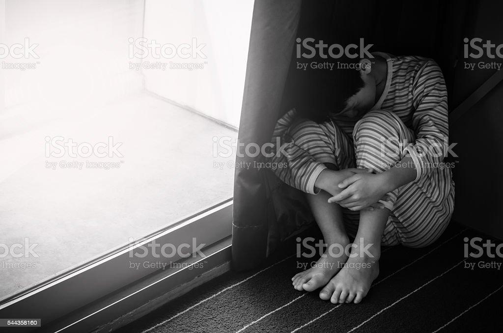 sad boy sitting on the floor stock photo