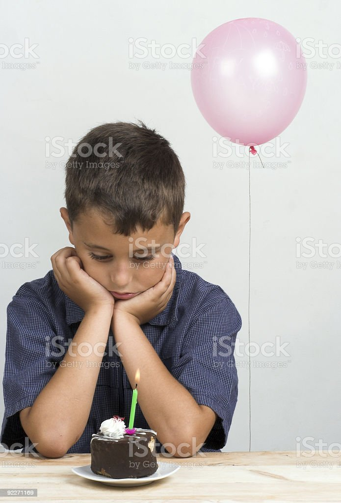 Sad boy starring at a small birthday cake with lit candle stock photo