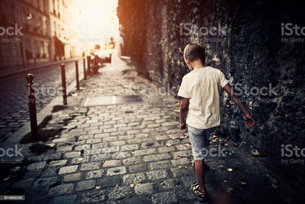 Sad boy walking sidewalk at Paris Montmartre stock photo