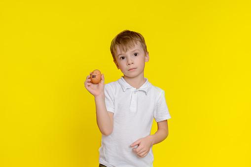 Sad boy with easter egg on yellow background