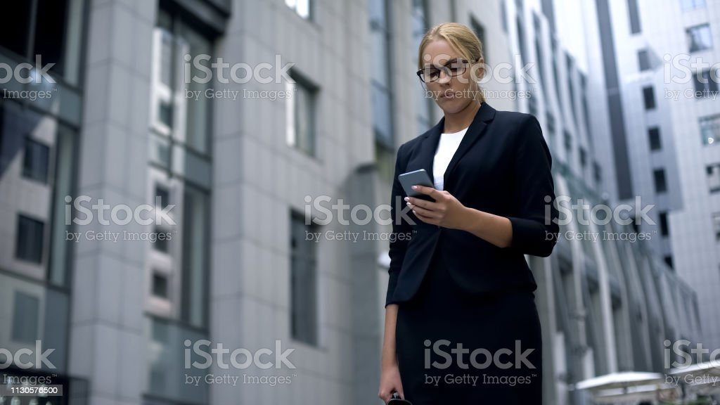 Sad business lady looking at phone, news about failed contract and...