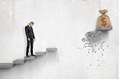 Sad businessman looking down on gray concrete staircase with big money bag at the top of it but with part of steps between businessman and bag missing. Big fail. Business problems. Hard way to top.