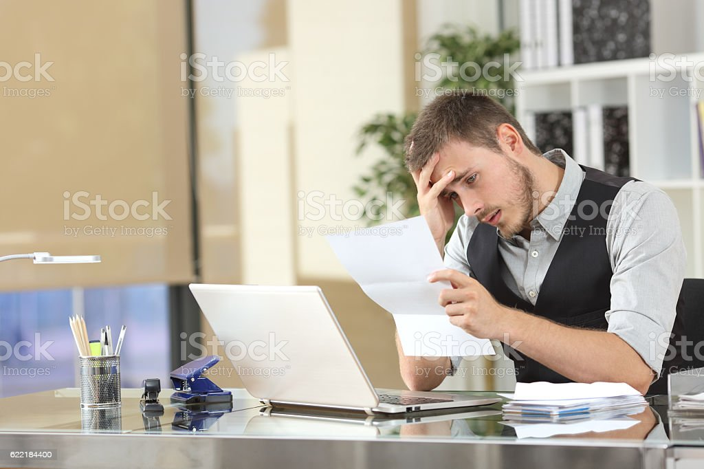 Sad businessman reading a letter at office stock photo