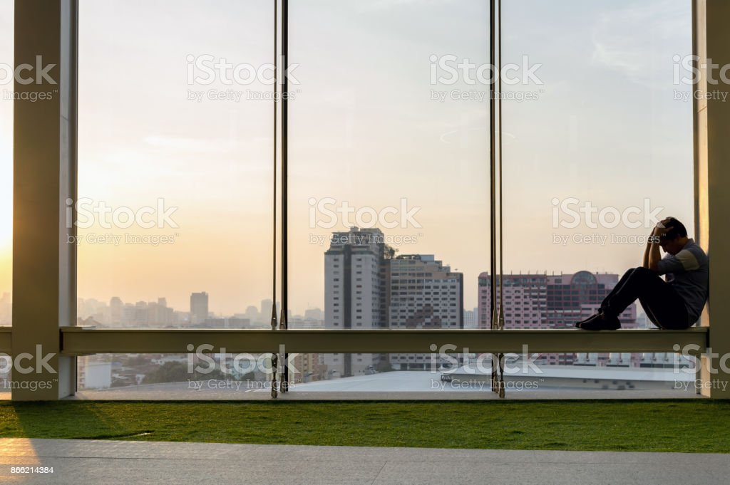 Sad businessman sitting head in hands on the the modern creative Office, dramatic concept stock photo