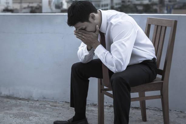 trauriger geschäftsmann sitzt draußen, besiegt. - bedauern stock-fotos und bilder