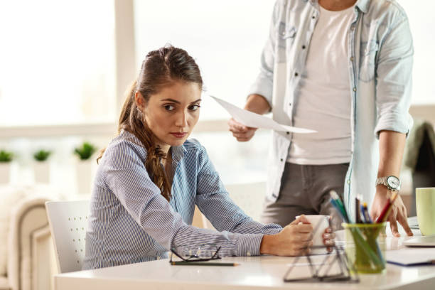 Sad businesswoman being scolded by her boss in the office. Young businesswoman looking away and thinking while her boss is scolding her at work. critic stock pictures, royalty-free photos & images