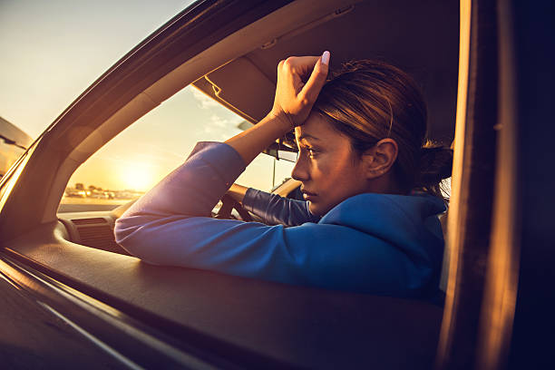 Sad businesswoman having problems while driving a car at sunset. stock photo
