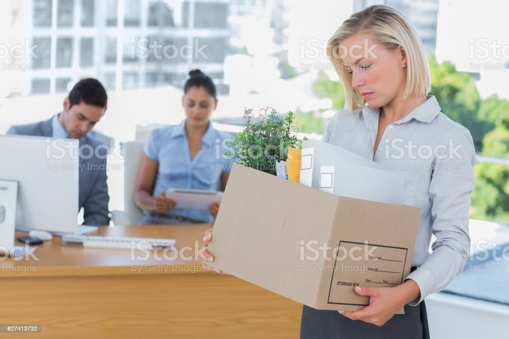 Sad businesswoman leaving office after being let go stock photo