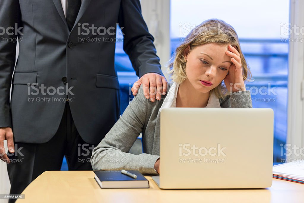 Sad businesswoman with her boss at background. Hand on shoulder stock photo