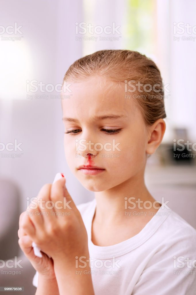 Sad cheerless girl looking at the paper tissue stock photo