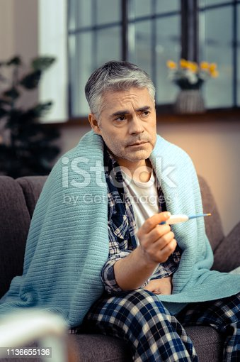Feeling bad. Sad cheerless man holding a thermometer while thinking about his illness