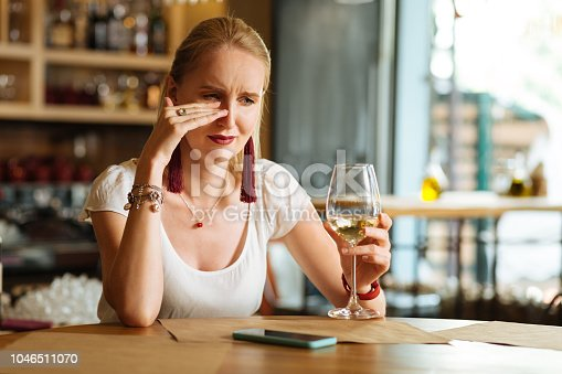 I am all alone. Sad cheerless woman drinking wine while crying in the restaurant