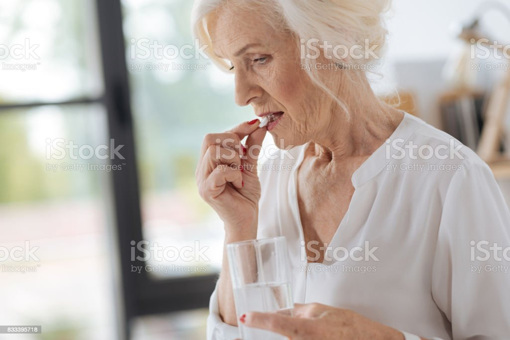 Sad cheerless woman putting a pill to her mouth stock photo