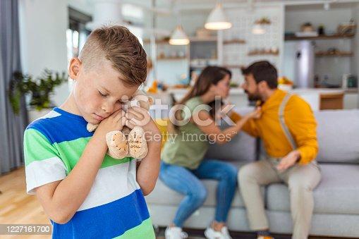 1166996783 istock photo Sad child boy embrace toy upset by parents arguing 1227161700