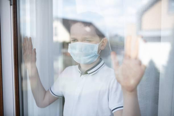 Sad child boy in medical mask looking through the window. Quarantine stock photo