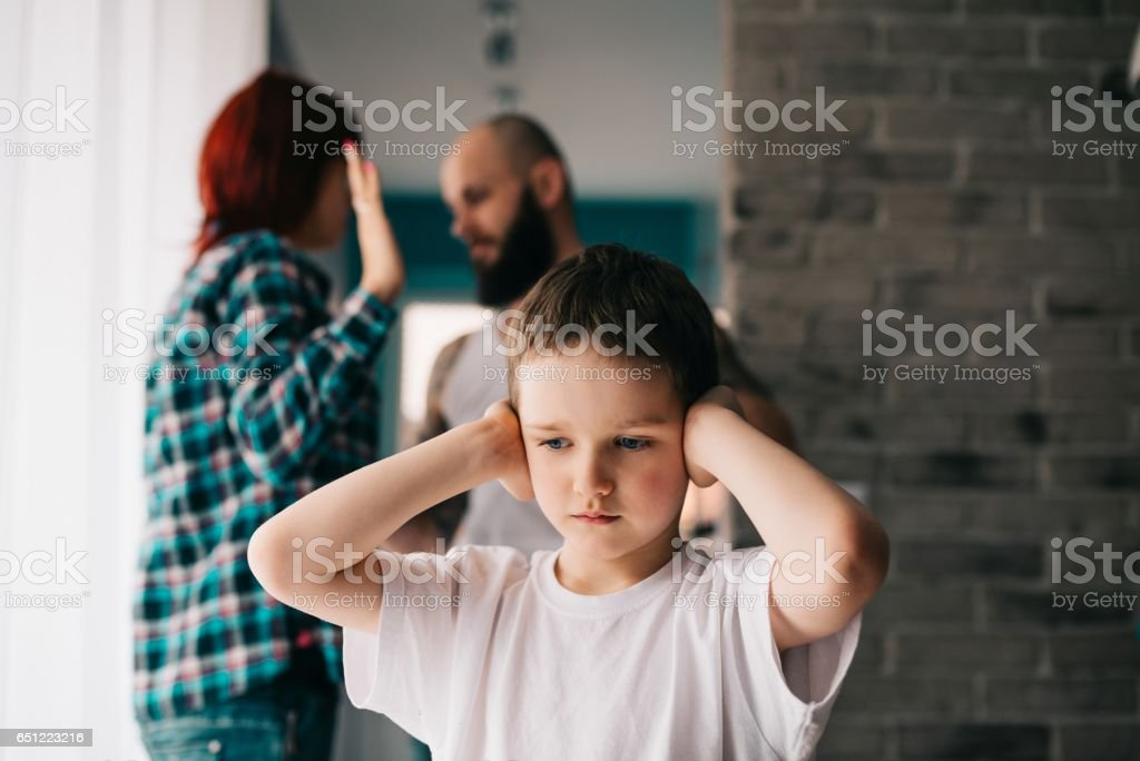 Sad child covering his ears with hands during parents quarrel. stock photo