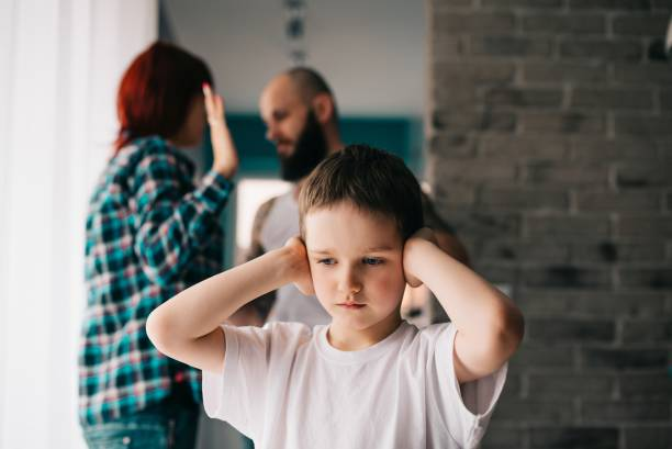 sad child covering his ears with hands during parents quarrel. - domestic violence stock pictures, royalty-free photos & images