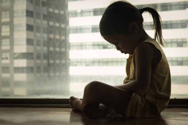 Sad child cryng alone. Depression. A litte girl sitting next to a window with her head down in sadness. Feeling depressed and hurt. face down stock pictures, royalty-free photos & images