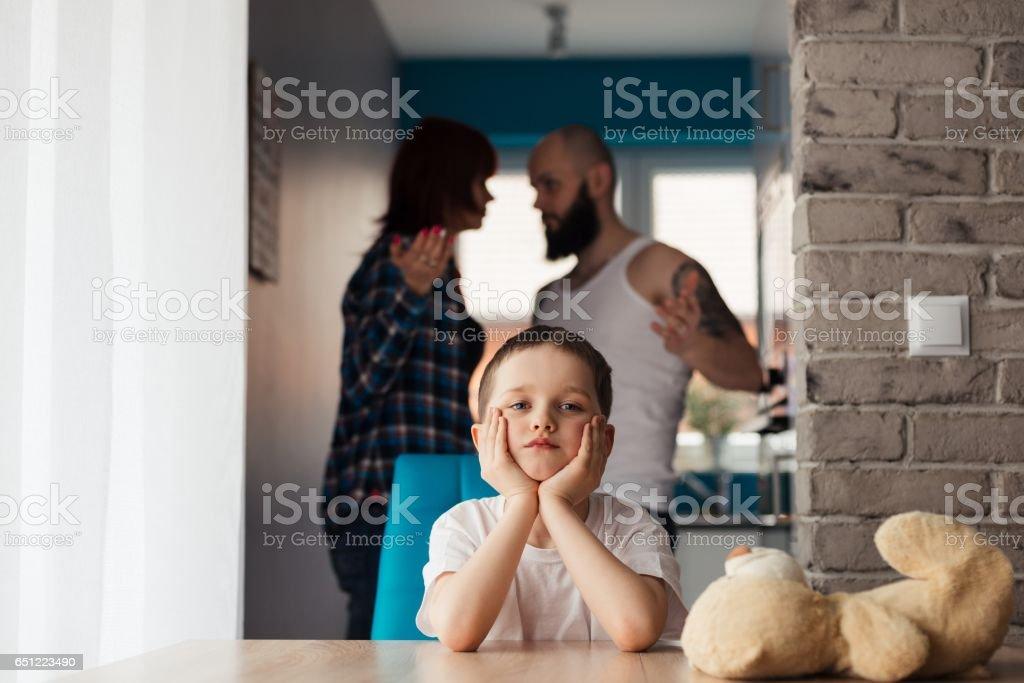Sad child during parents quarrel stock photo