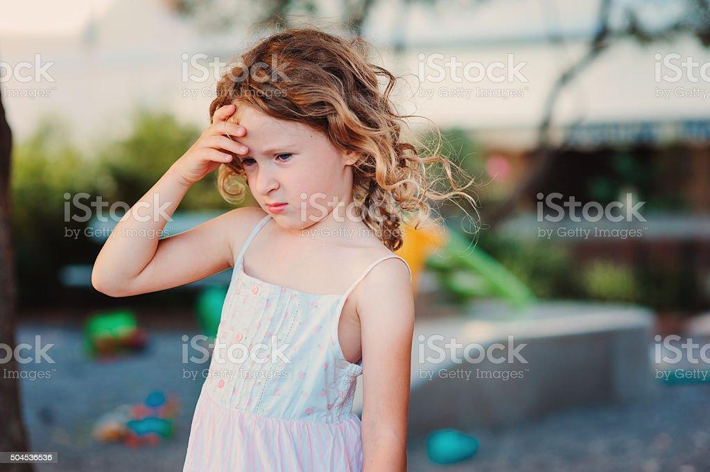 sad child girl with headache on playground stock photo