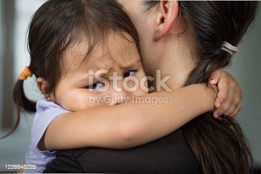 A sad little girl hugging her parent to feel safe, tearful.