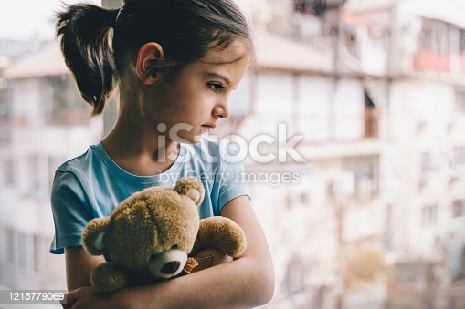 Sad child in home quarantine  at the window holding teddy bear. Coronavirus COVID-19.