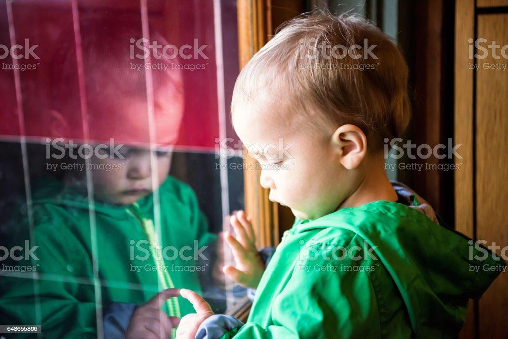 Sad child looking through a window stock photo