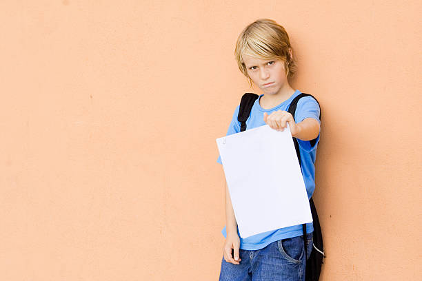 sad child showing bad exam results stock photo