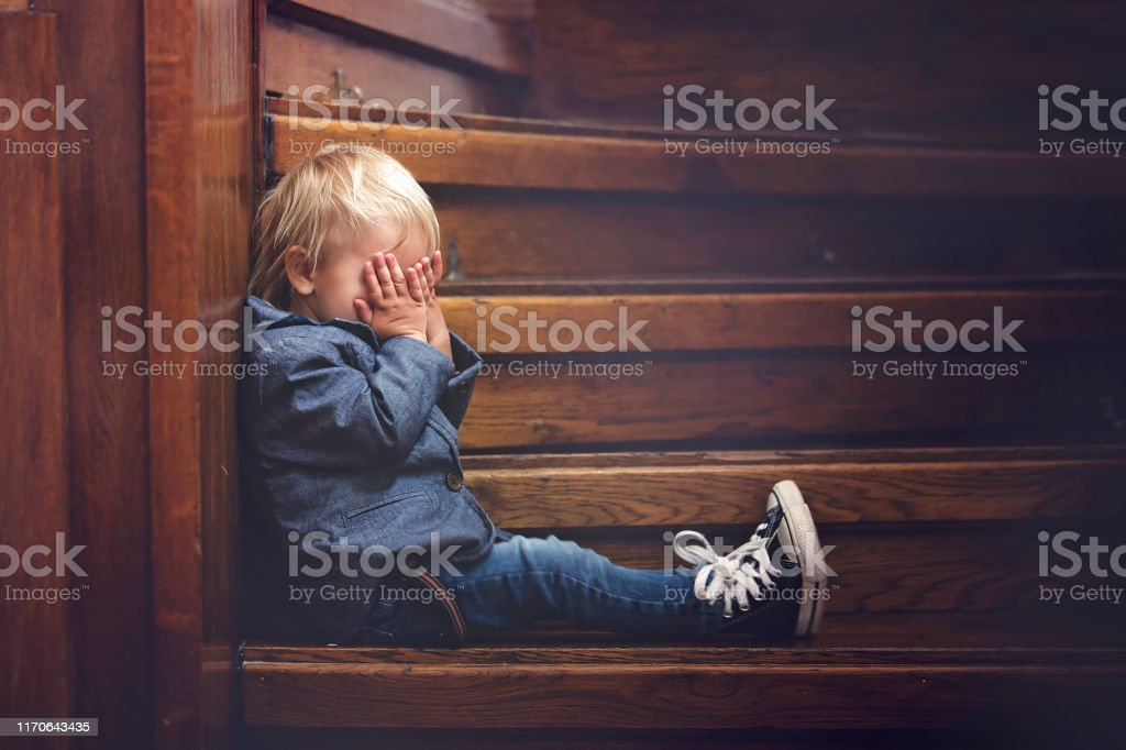 Niño triste, sentado en una escalera en una casa grande, concepto para el acoso escolar, depresión - Foto de stock de Abandonado libre de derechos