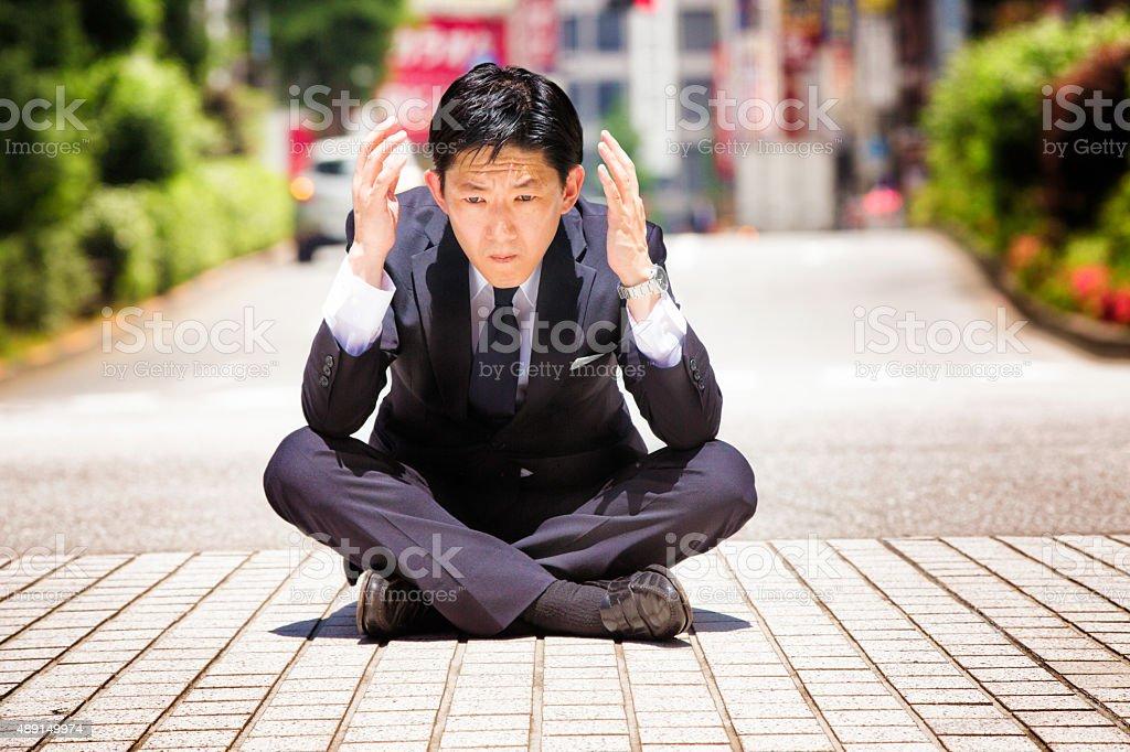Sad confused Japanese businessman sits on the sidewalk stock photo