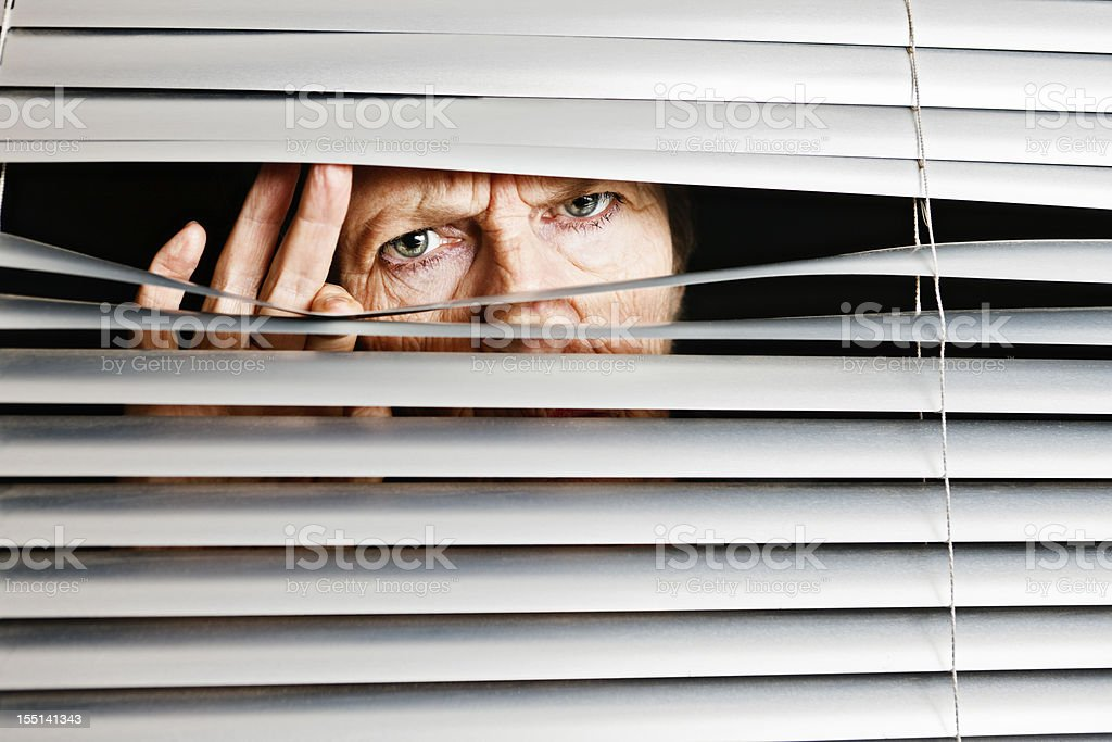 Sad confused old woman peeps through venetian blinds stock photo
