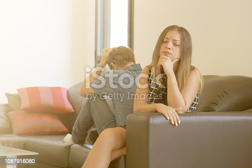istock Sad couple after argument or breakup sitting on a sofa in the living room in a house indoor. 1087916080