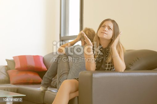istock Sad couple after argument or breakup sitting on a sofa in the living room in a house indoor. 1087916312