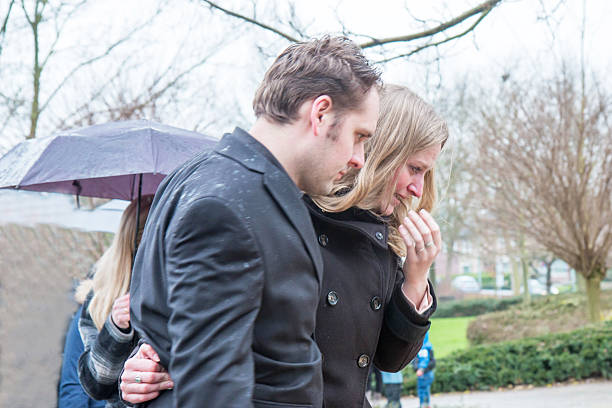 sad couple at a funeral - funeral crying stockfoto's en -beelden