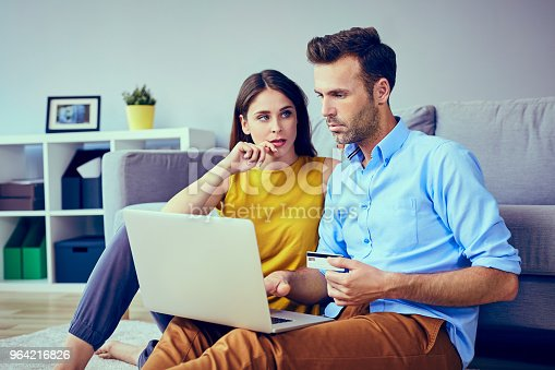 istock Sad couple doing online payments  on their laptop at home 964216826