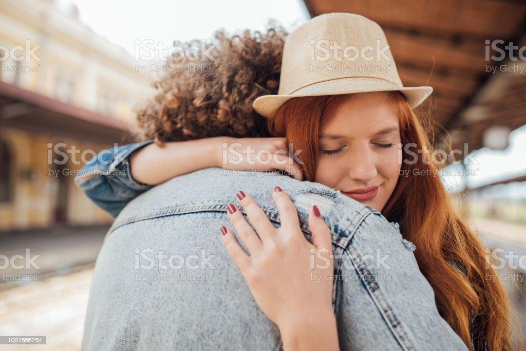 Sad couple hugging while saying goodbye Couple separating on train station Adult Stock Photo