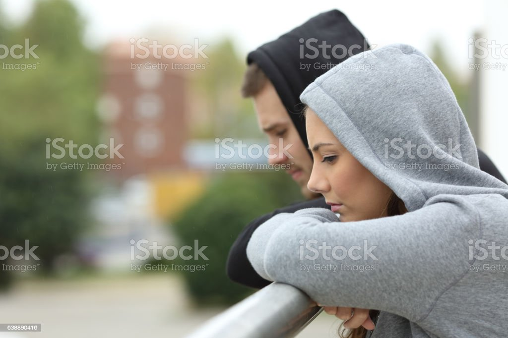 Sad couple of teens looking down in a balcony stock photo