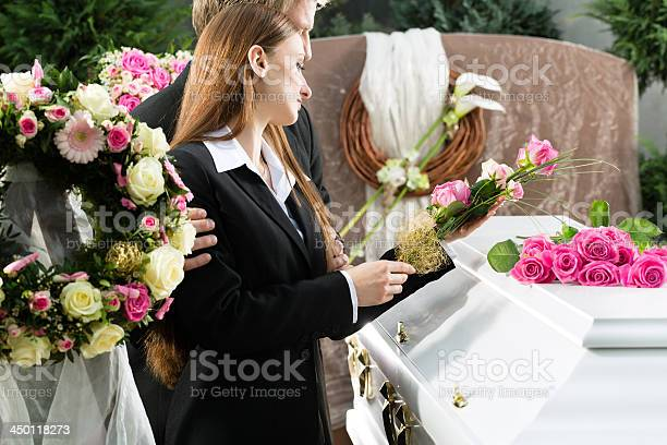 Sad couple placing flowers on a white casket at a funeral picture id450118273?b=1&k=6&m=450118273&s=612x612&h= hyjmujggeuewsfvk4cyhqgn662padclzljddo0n5na=