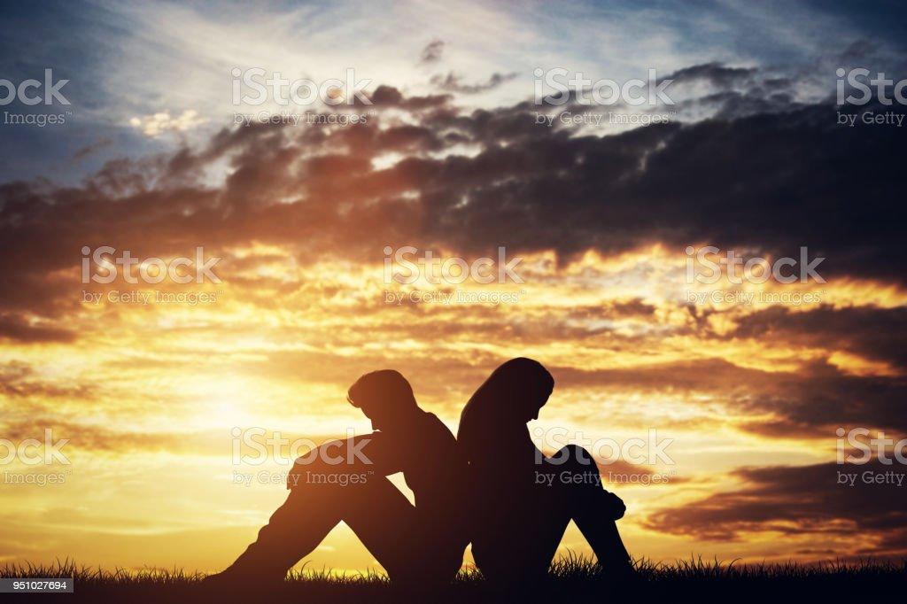 Sad couple sitting back-to-back on a ground. stock photo