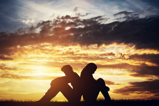 sad couple sitting back-to-back on a ground. - relationship difficulties stock pictures, royalty-free photos & images