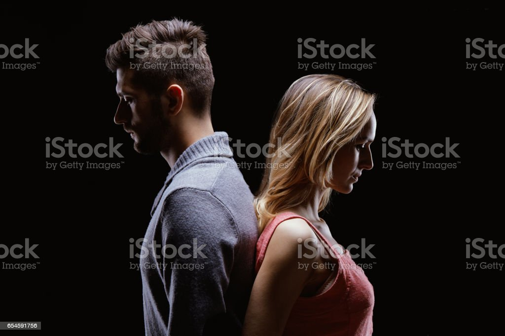 Sad couple standing back to back stock photo