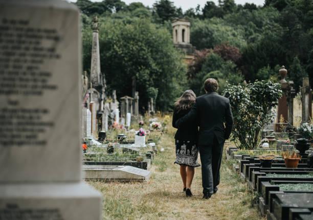 sad couple walking through a cemetery - funerale foto e immagini stock