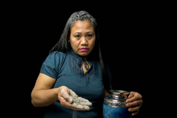 traurig weinen asiatischen weiblichen streuung geliebten der eingeäscherten asche von a aus einer urne auf beerdigung - trauer abschied tod stock-fotos und bilder