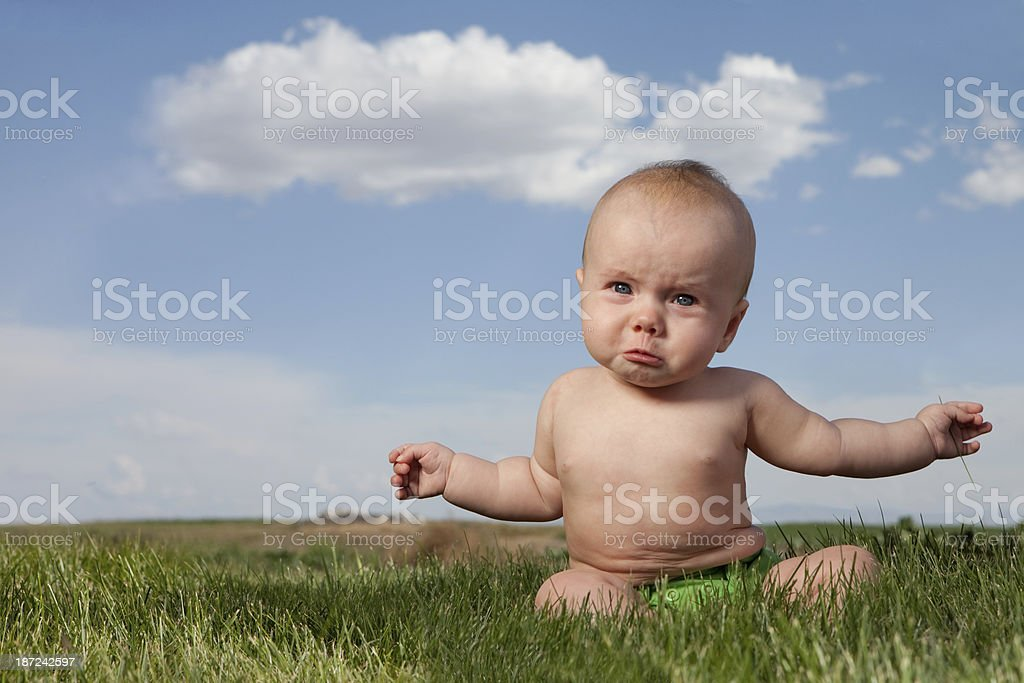 Sad Crying Baby Sitting Outdoors on Grass stock photo