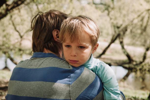 traurig weinende sohn umarmt vater - emoticon hug stock-fotos und bilder