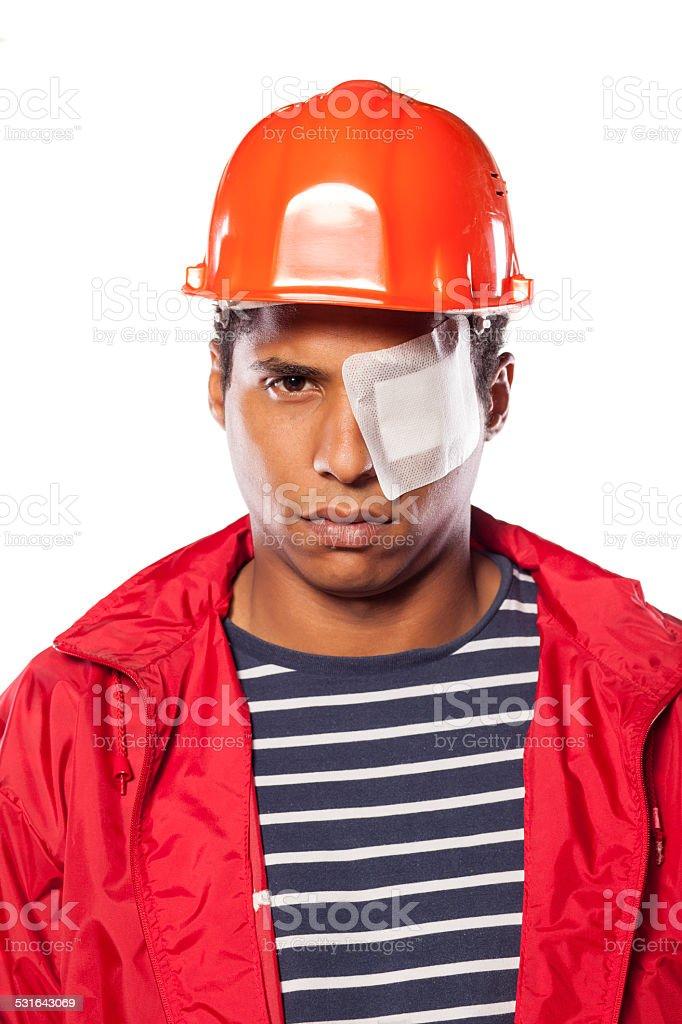 Sad dark-skinned worker with helmet and injured eye stock photo