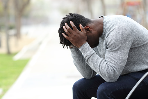 Side view portrait of a sad depressed black man sitting on a bench in a park